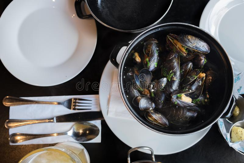 Belgian lunch: steamed mussels, french fries and beer. On black table royalty free stock images