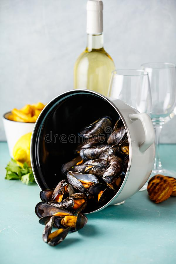 Belgian mussels in white wine with lemon, herbs, croutons and french fries stock photo