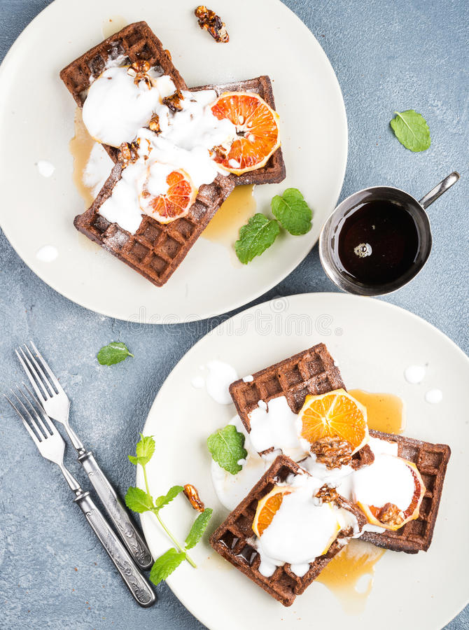 Belgian soft waffles with blood orange, cream, marple syrup and mint on white plates stock photography