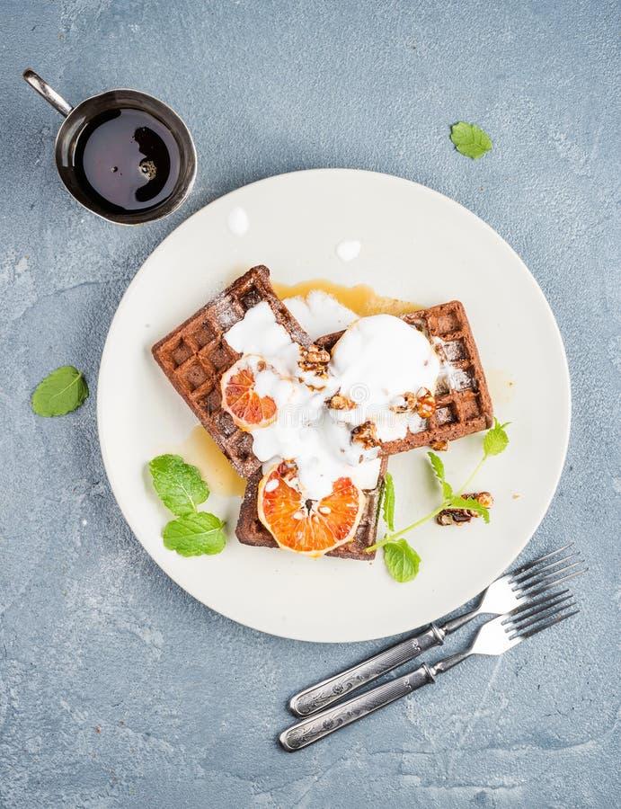 Belgian soft waffles with blood orange, cream, marple syrup and mint on white plates stock photo