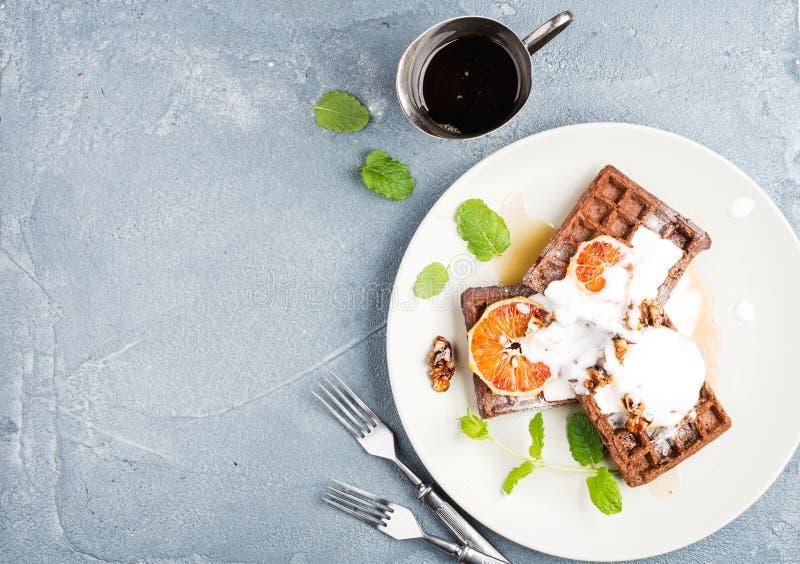 Belgian soft waffles with blood orange, cream, marple syrup and mint on white plates stock image