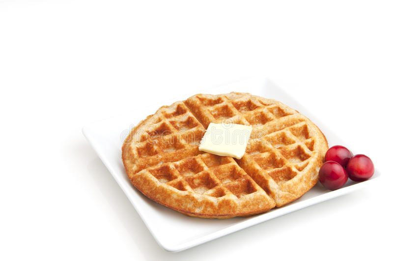 Belgian Waffle. Fresh made Belgian waffle with pat of butter and just picked cherries royalty free stock photos