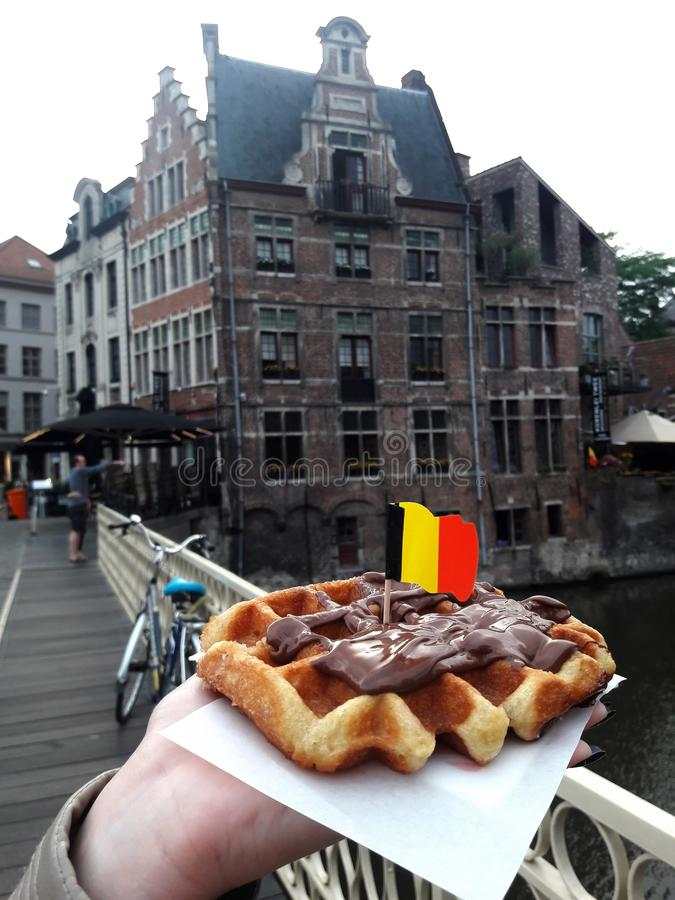 Belgian waffle. On the background of the old European city of Ghent royalty free stock photography