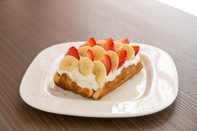 Belgian waffle with banana and strawberry. Belgian waffle with wipped cream, banana and strawberry. Selective focus, narrow depth of field stock photo
