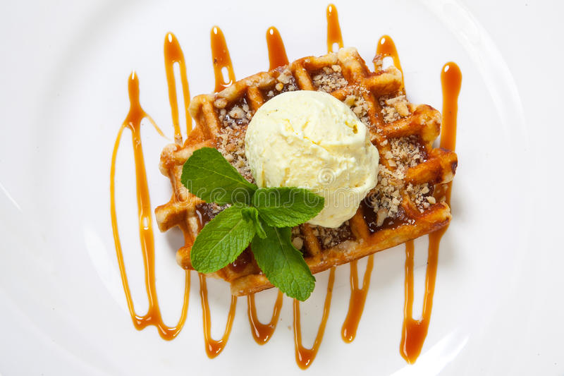 Belgian waffle with ice cream, caramel and mint.  royalty free stock photos