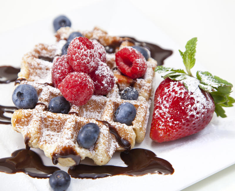 Belgian waffle with powdered sugar, chocolate syrup, and fruit o. N white royalty free stock photography