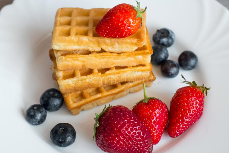 Belgian waffles. With Strawberry and Blueberries on white blate close up royalty free stock photos