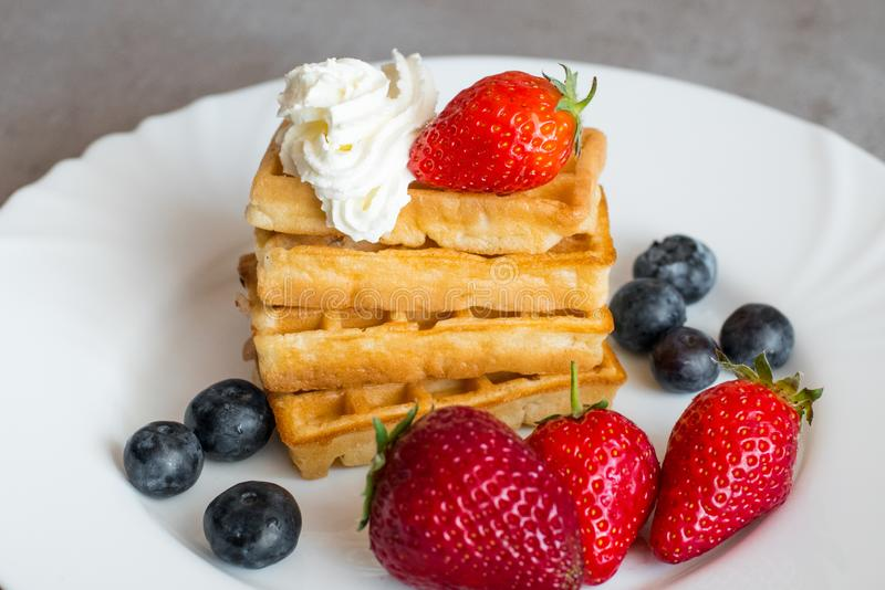 Belgian waffles. With Strawberry and Blueberries on white blate close up royalty free stock images
