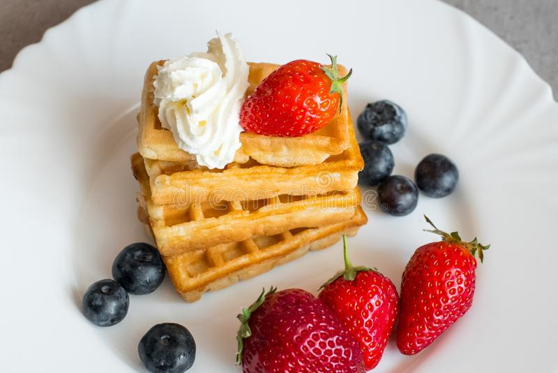 Belgian waffles. With Strawberry and Blueberries on white blate close up royalty free stock photo