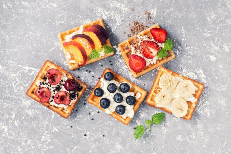 Belgian waffles with berries and fruit on a grey background. The view from the top,flat lay. stock images