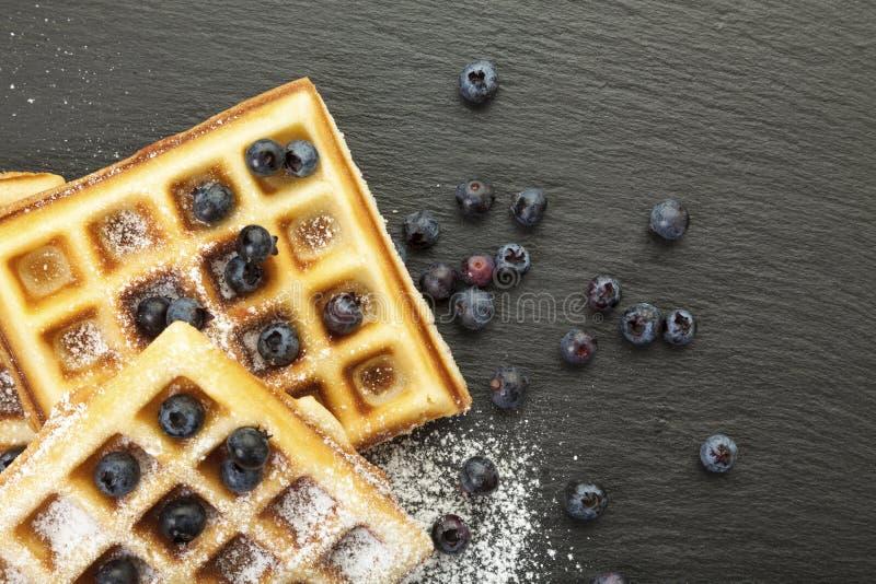 Belgian waffles with blueberries on black slate. Handmade belgian waffles with blueberries and icing sugar on black slate, closeup stock image