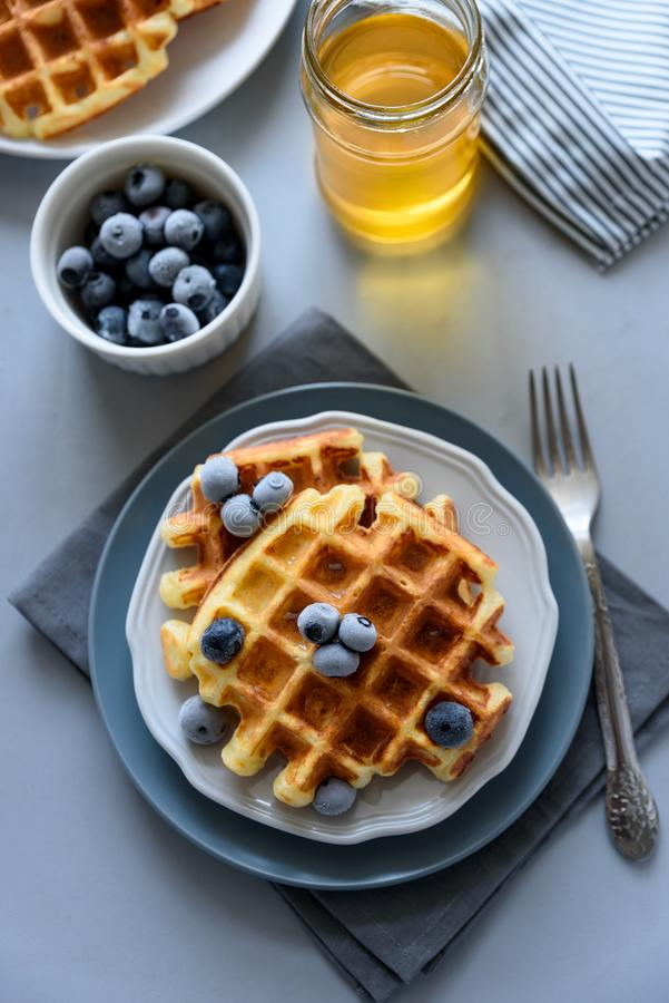 Belgian waffles with blueberries and honey on gray wooden background. Homemade healthy breakfast. Selective focus royalty free stock photo