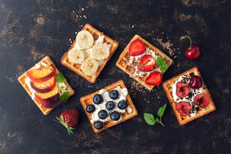 Belgian waffles with blueberries,strawberries,peaches, cherries and banana. Homemade waffles on a dark rustic background. The view stock image