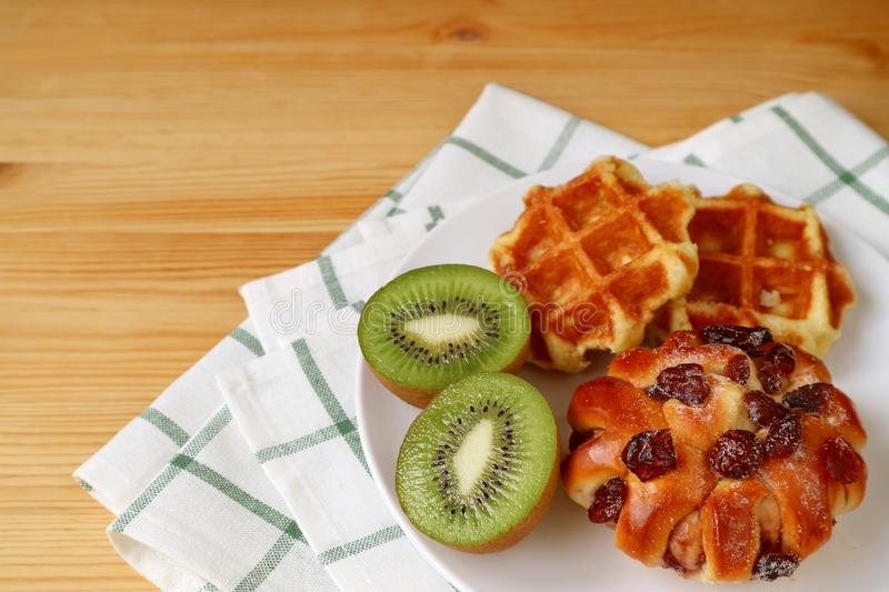 Belgian waffles and cranberry bun with cut kiwi fruit on a white plate served on wooden table royalty free stock photos