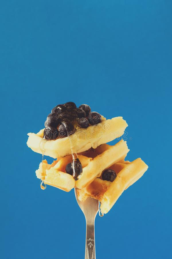 Belgian waffles with honey and blueberry pinned on a fork stock photography