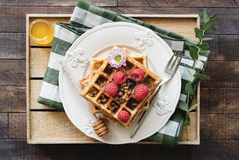 Belgian waffles with honey and raspberries for breakfast. Waffles decorated with flower, berries, granola and honey on wooden serving tray. Top view royalty free stock image