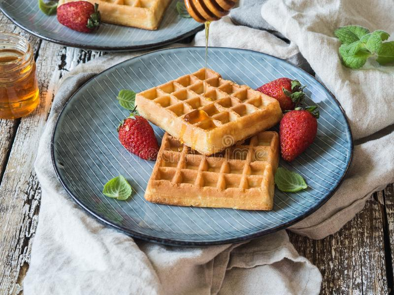 Belgian waffles with honey and strawberries on a blue plate stock photos