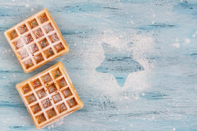 Belgian waffles with icing sugar and confectionery sprinkles on the table. Christmas and New Year mood. Powdered sugar star. Top view stock image