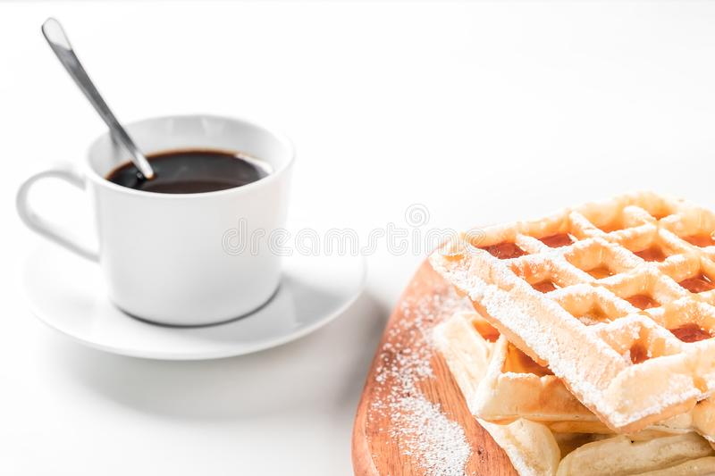 Belgian waffles with icing sugar and maple syrup. On the white table stock photos