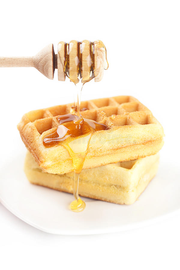 Belgian waffles on a plate, stick for honey and honey. Isolated on white stock image