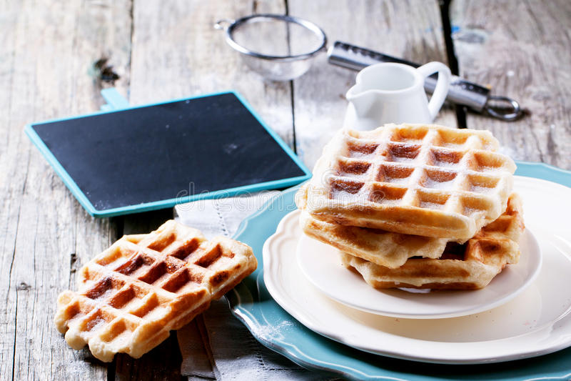 Belgian waffles. Plates with fresh belgian waffles served with empty black chalkboard over old wooden table. See series stock photography