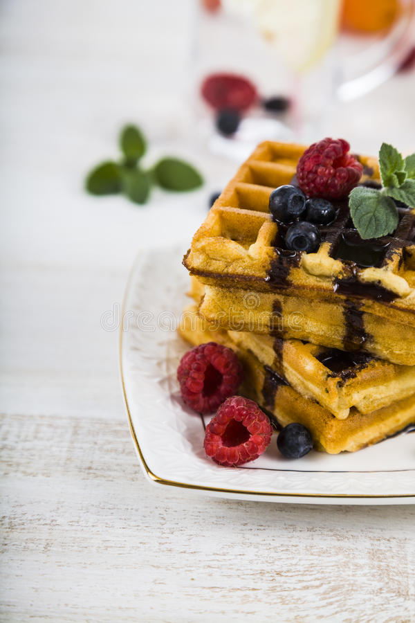 Belgian waffles with raspberries, blueberries and mint, covered royalty free stock images