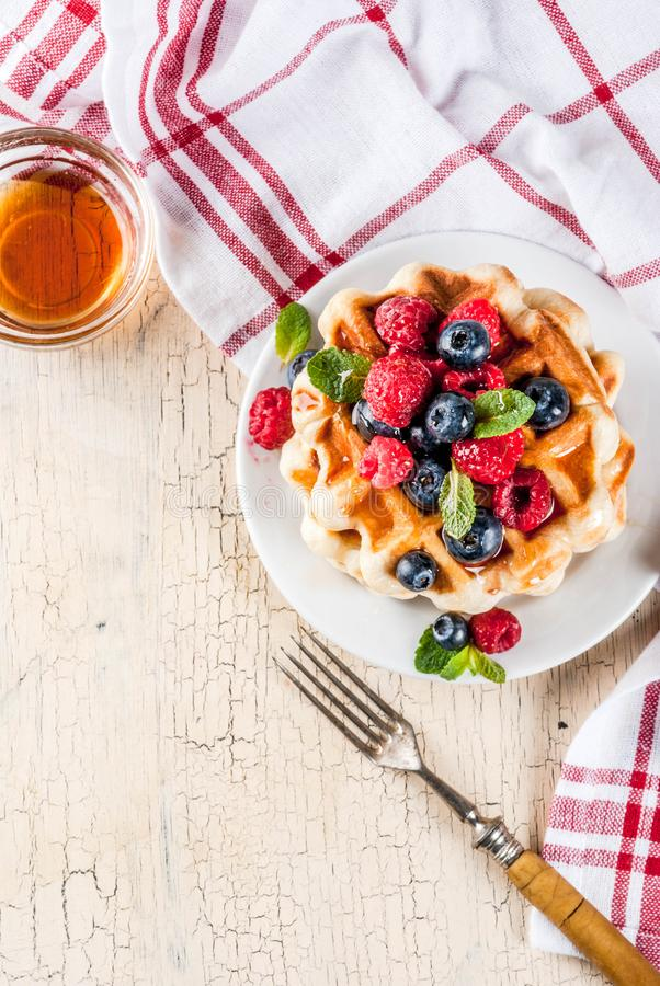 Belgian waffles with raspberries, blueberries and syrup, homemade healthy breakfast, light concrete background copy space royalty free stock photo