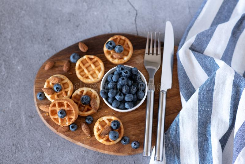 Belgian waffles with raspberries, blueberries and syrup, homemade healthy breakfast, light concrete background copy space royalty free stock image