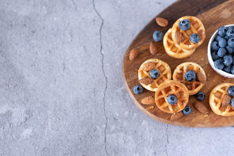 Belgian waffles with raspberries, blueberries and syrup, homemade healthy breakfast, light concrete background copy space stock photo