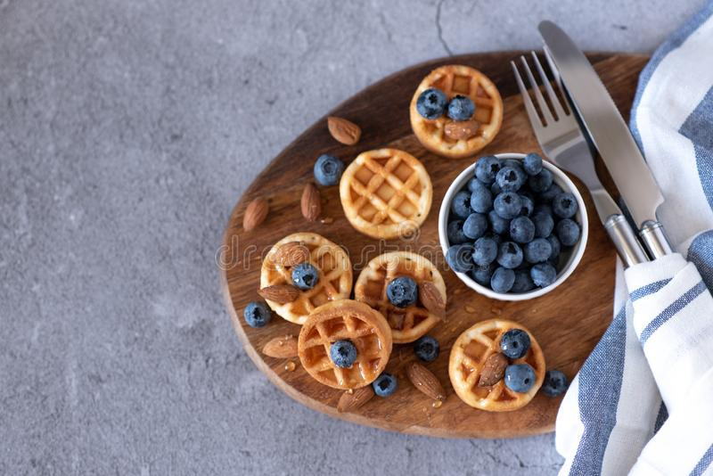 Belgian waffles with raspberries, blueberries and syrup, homemade healthy breakfast, light concrete background copy space.  royalty free stock photos