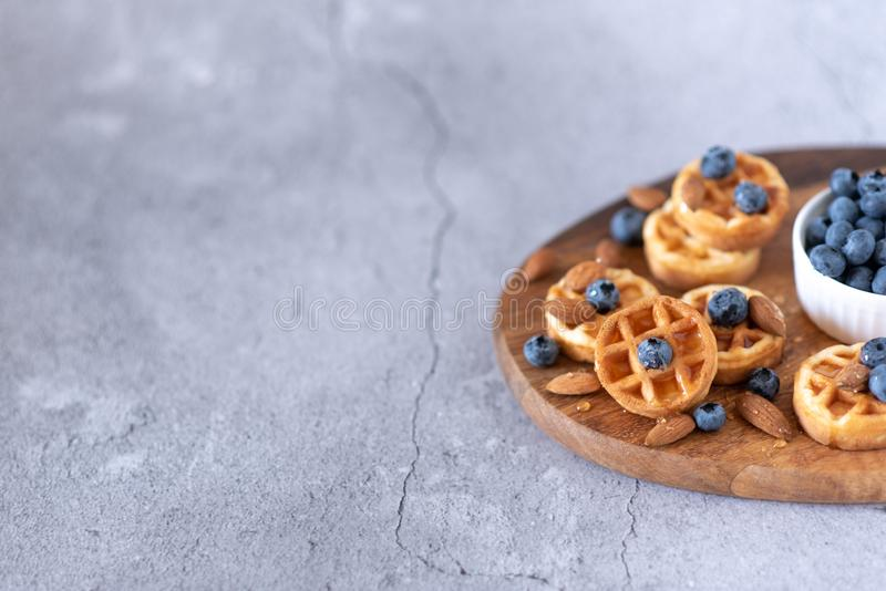 Belgian waffles with raspberries, blueberries and syrup, homemade healthy breakfast, light concrete background copy space stock photos
