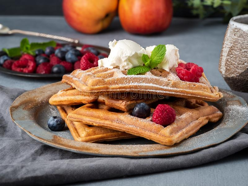 Belgian waffles with raspberries, chocolate syrup. Breakfast with tea on dark background, side view, close-up royalty free stock photos