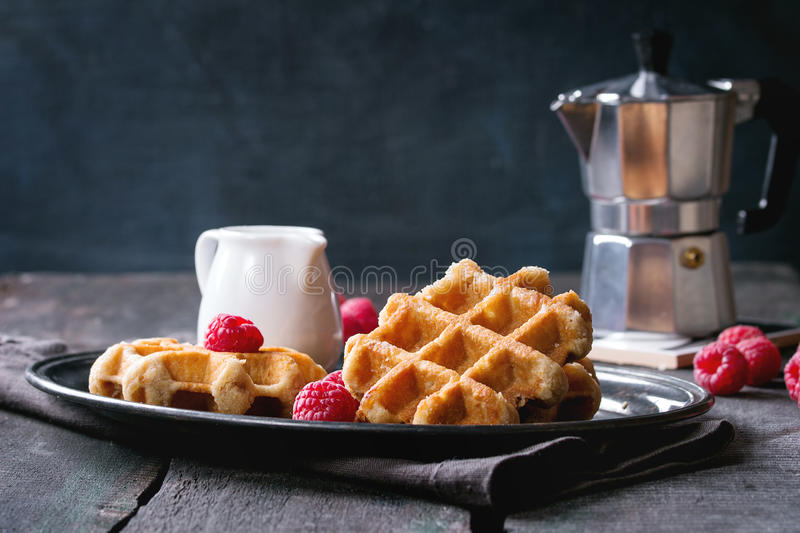 Belgian waffles with raspberries. Served with coffee pot and jug of milk on vintage tray over old wooden table royalty free stock photo