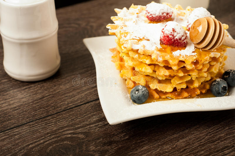 Belgian waffles with raspberries and sieving sugar powder and honey served with jug of milk on a white table royalty free stock photos