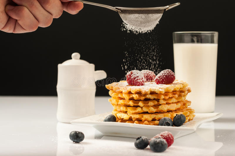 Belgian waffles with raspberries and sieving sugar powder and honey served with jug of milk on a white table.  royalty free stock photo
