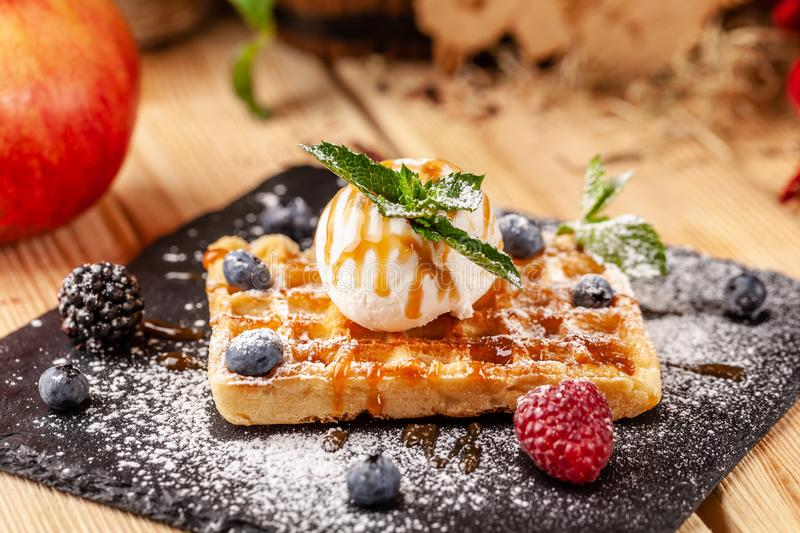 Belgian waffles with a scoop of ice cream, fresh berries raspberries, blackberries, blueberries and mint. Dusted with icing sugar royalty free stock photography
