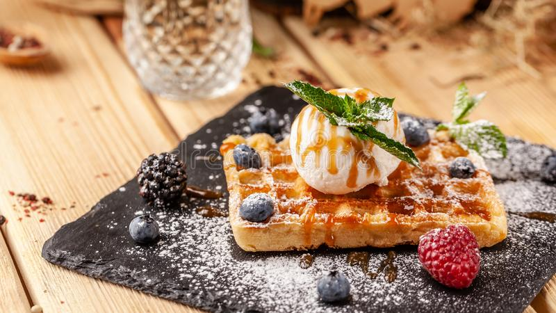 Belgian waffles with a scoop of ice cream, fresh berries raspberries, blackberries, blueberries and mint. Dusted with icing sugar. And poured over caramel sauce stock photo