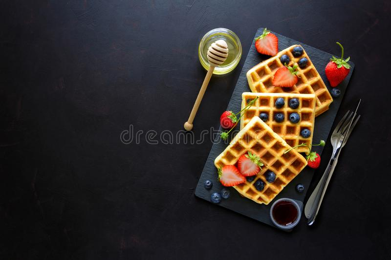 Belgian waffles with strawberries, blueberries and honey on slate plate on dark wooden background. Top view. Copy space royalty free stock image