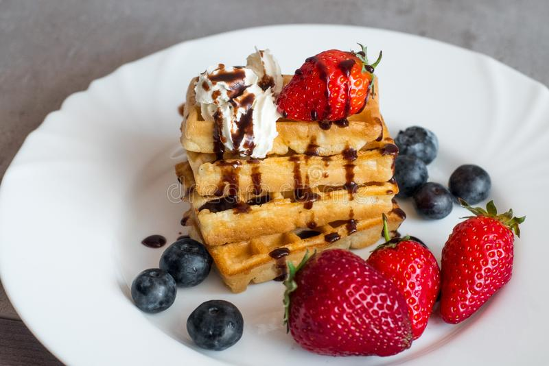 Belgian waffles. With Strawberry and Blueberries on white blate close up stock photos
