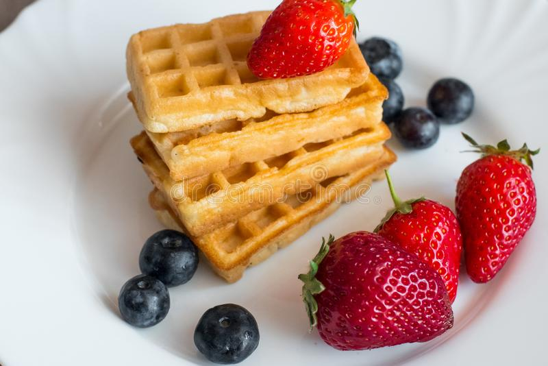 Belgian waffles. With Strawberry and Blueberries on white blate close up stock photography