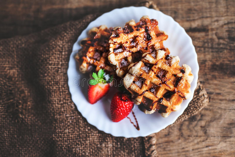 Belgian waffles topped with strawberries, syrup and icing. Homemade breakfast in rustic style, toned image with copy space . royalty free stock photo