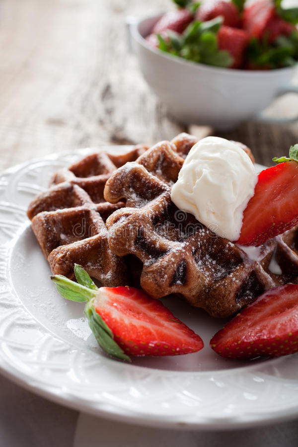 Belgian waffles. With vanilla ice cream and strawberries royalty free stock image