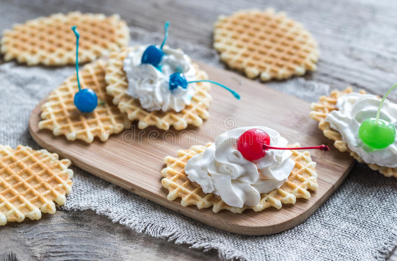 Belgian waffles with whipped cream. Decorated with cocktail cherries royalty free stock photos