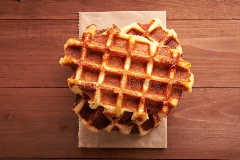 Belgian waffles on a wooden table. Belgian waffles on a brown wooden table royalty free stock photos