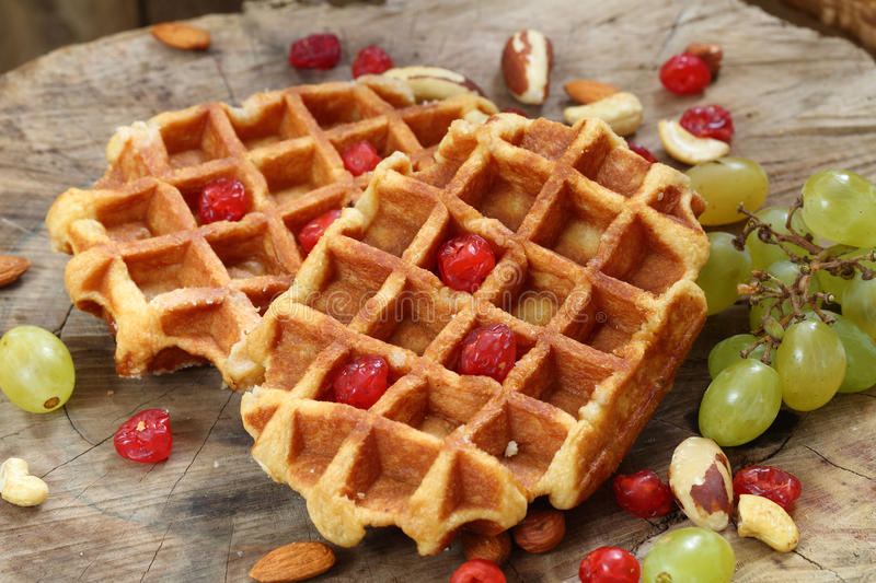 Belgian waffles on a wooden table. Belgian waffles with grapes and nuts on a wooden table royalty free stock images