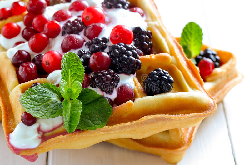 Belgian waffles with yogurt and berries. Breakfast with freshly baked belgian waffles with yogurt and berries royalty free stock photography