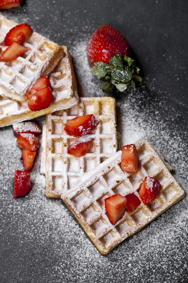 Belgien rån med jordgubbar och sockerpulver på svart bräde royaltyfri foto