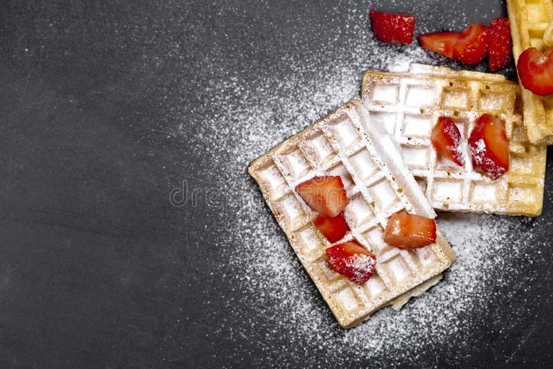 Belgien rån med jordgubbar och sockerpulver på svart brädebakgrund royaltyfri foto