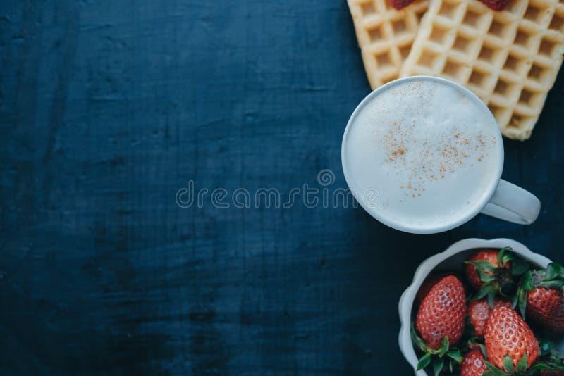Belgijscy gofry, truskawki i cappuccino w białym kubku, przestrzeń zdjęcia royalty free