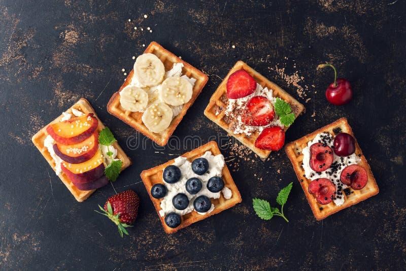 Belgijscy gofry z czarnymi jagodami, truskawkami, brzoskwiniami, wiśniami i bananem, Domowej roboty gofry na ciemnym nieociosanym obraz stock